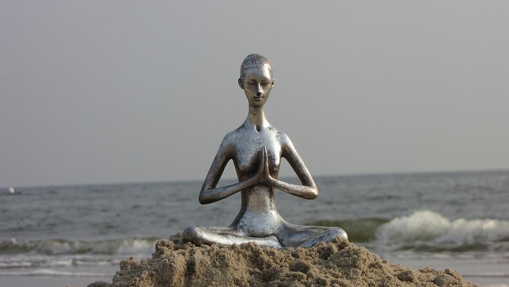 Statuette argentée en position du lotus placée sur un rocher dos à la mer