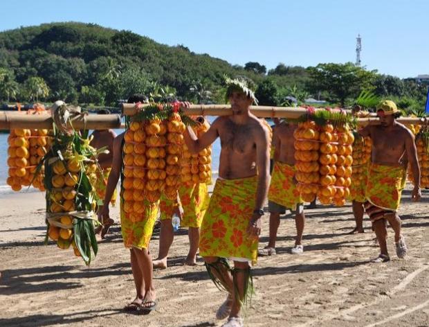 Hommes portant des grappes d'orange sur un bambou