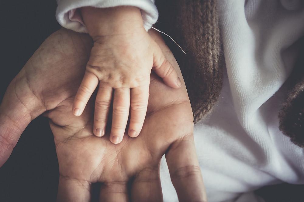 Une main d'enfant dans une main d'adulte