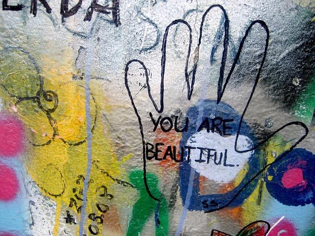 """Un mur couvert de graffitis colorés, le contour d'une main avec écrit en son centre """" You're beautiful """""""