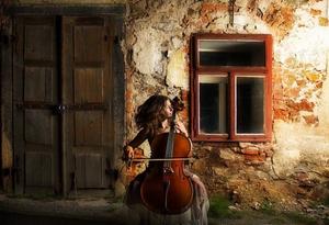 Femme jouant du violoncelle devant une maison ancienne, entre la porte et la fenêtre