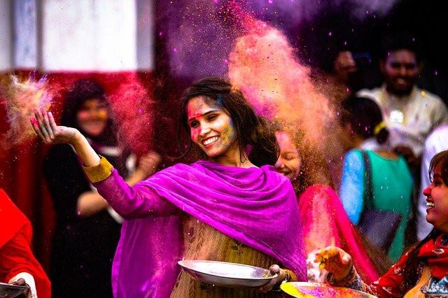 Jeune femme souriante en habits colorés jette de la poudre rose dans une foule colorée, émotion de joie