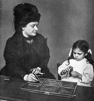 Maria Montessori guide une petite fille en apprentissage