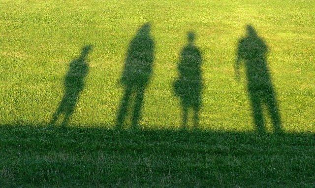 Silhouettes d'une famille de quatre personnes sur fond d'herbe