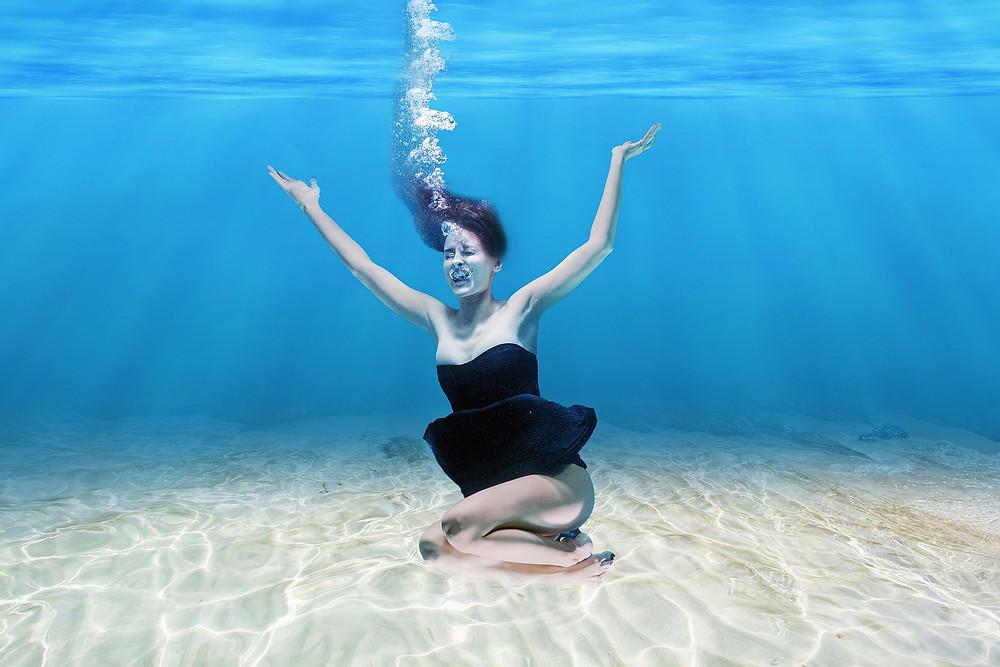 Une femme au fond de la piscine fait dse bulles