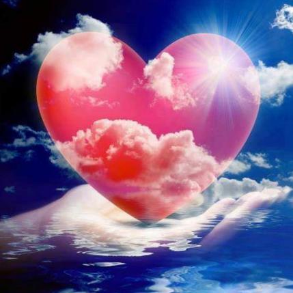 Cœur rose dans la paume d'une main sur fond de ciel
