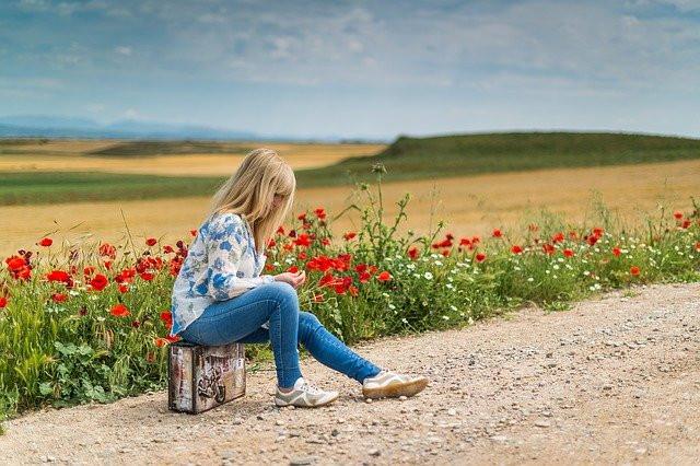 Jeune fille blonde assise sur sa valise en bord de route