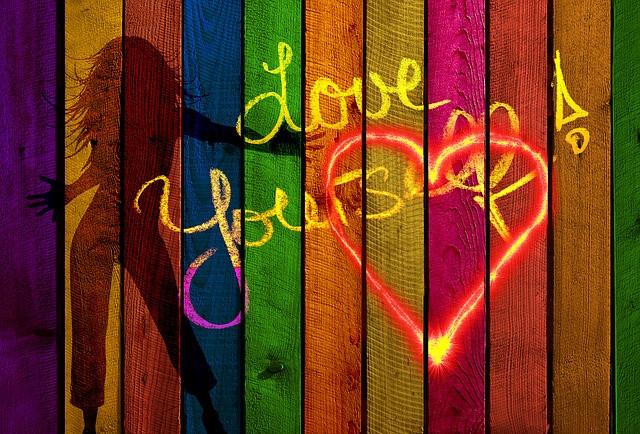 Lattes de bois de couleurs, une silhouette de femme et écrit à la craie jaune : Love yourself ! avec un cœur