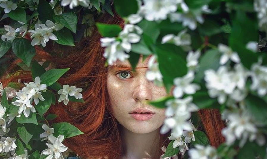 Visage de femme à moitié caché derrière des feuilles et des fleurs
