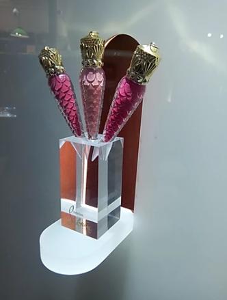 Trois flacons de couleurs roses dans un présentoir de cristal suspendu en vitrine