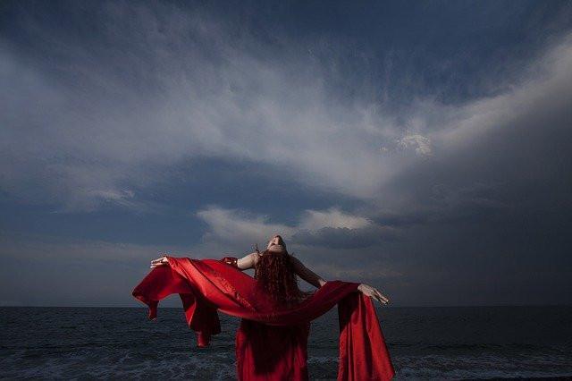 Une femme, ployée en arrière face au ciel , une étole rouge recouvre ses bras