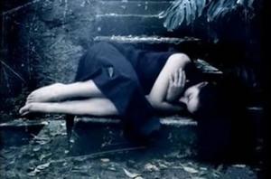Femme en robe bleue couchée en fœtus sur un banc
