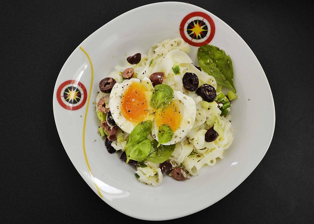 assiette sans gluten avec œuf, pâtes de riz, olives et verdure