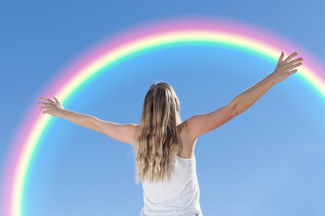 Une femme de dos, bras écartés fait face à un arc en ciel