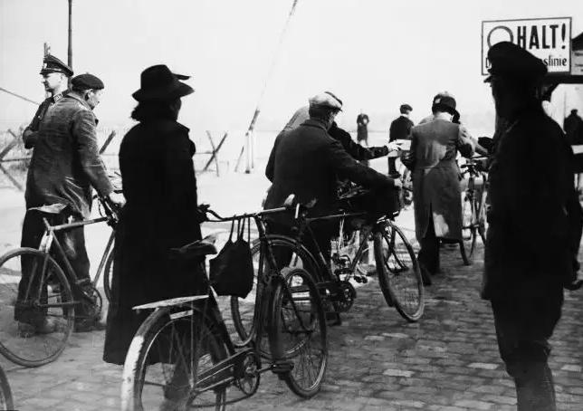Des hommes, des femmes à vélo passent la barrière de contrôle en 1942
