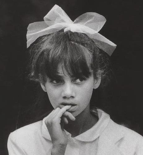 Photographie de Sabine Weiss, une petite fille mordille son petit doigt, un gros ruban blanc dans les cheveux