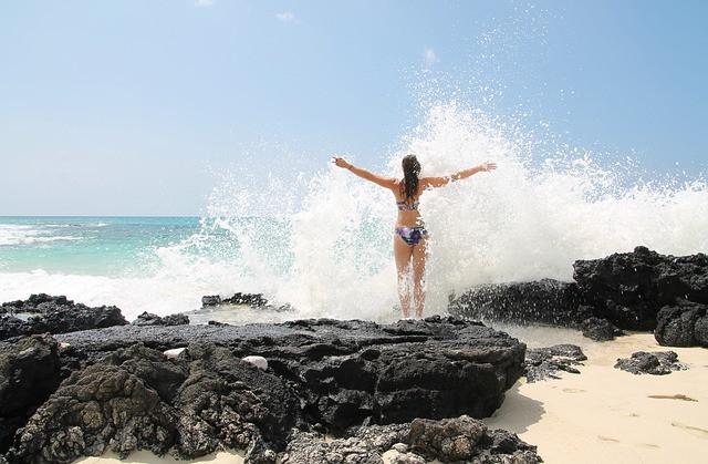 Femme de dos sur un rocher, faisant face à la vague