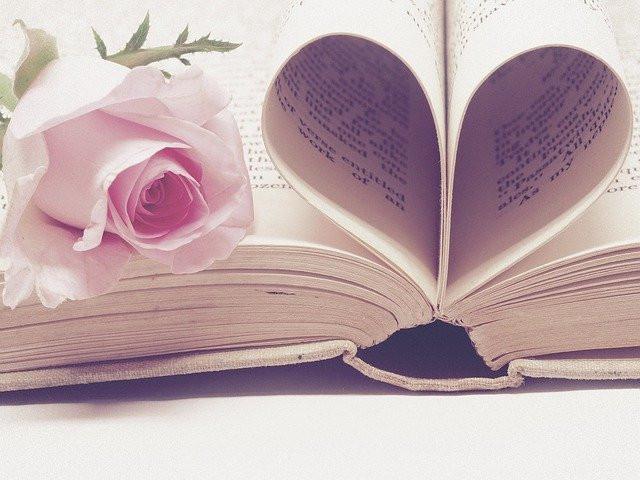 Livre ouvert, une rose sur la page de gauche, les pages du centre forment un cœur