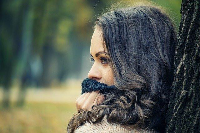 Jeune femme de profil appuyée contre un arbre, le col de son pull devant sa bouche  pour étouffer ses émotions