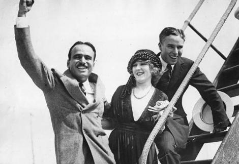 Sur la passerelle d'un avion, Douglas Fairbanks salue en levant la main tenu par la taille par Mary Pickford, accompagnée par Charlie Chaplin