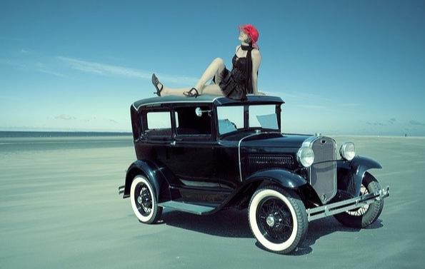 Une traction noire des années 1920, une femme est assise sur le toit, jambes croisées