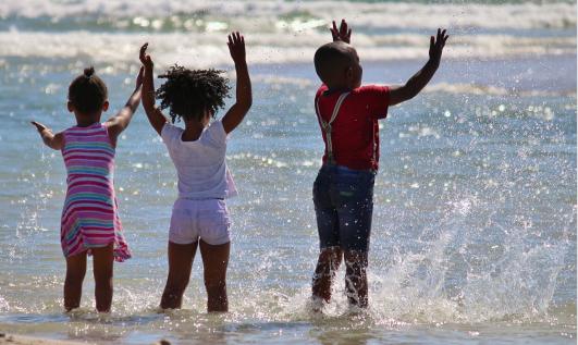Trois enfants face à la mer lèvent les bras