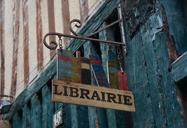 Enseigne ancienne de librairie accrochée à une maison à colombages