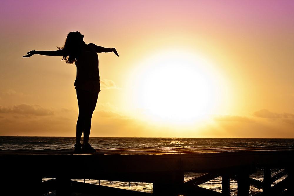 Femme bras ouverts devant le soleil couchant