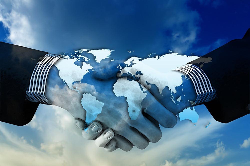 Deux mains se croisent dans l'espace, la carte du monde se reflète sur elles