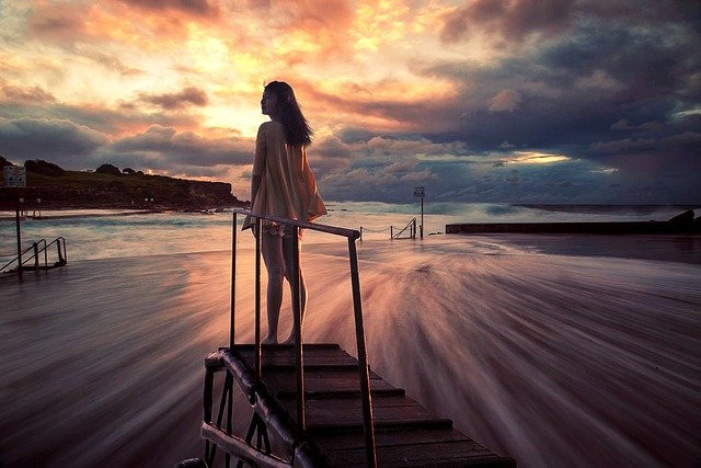 Jeune femme sur un pont face à la mer et au soleil couchant, prête à gérer ses émotions