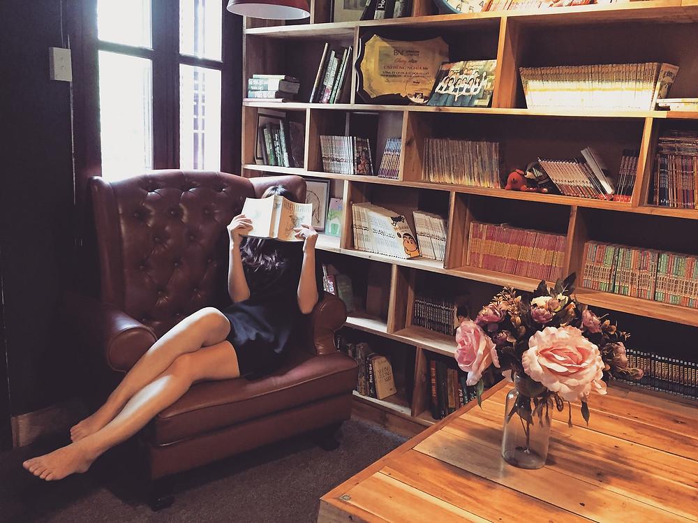 Une femme lit, confortablement installée dans un canapé