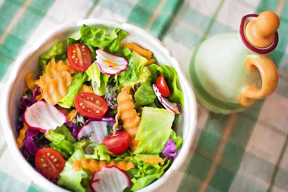 Un bol blanc contenant une salade colorée de crudités, à côté une flacon d'huile
