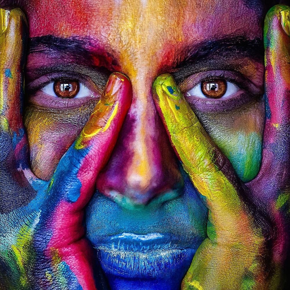 Visage de femme peint de couleurs multiples