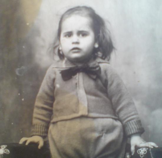 Photo de Léon enfant, un nœud orne son col, cheveux longs et mains posées de chaque côté