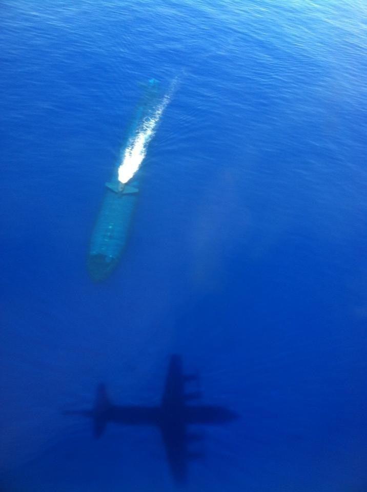 Avión sobrevolando un submarino