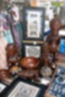 Detail inrichting kraam Galerie Caroline met tapa, houtsnijwerk, kokosnoot en sieraden