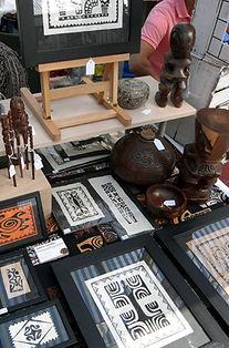 Detail inrichting kraam Galerie Caroline met tapa, houtsnijwerk, kokosnoot...