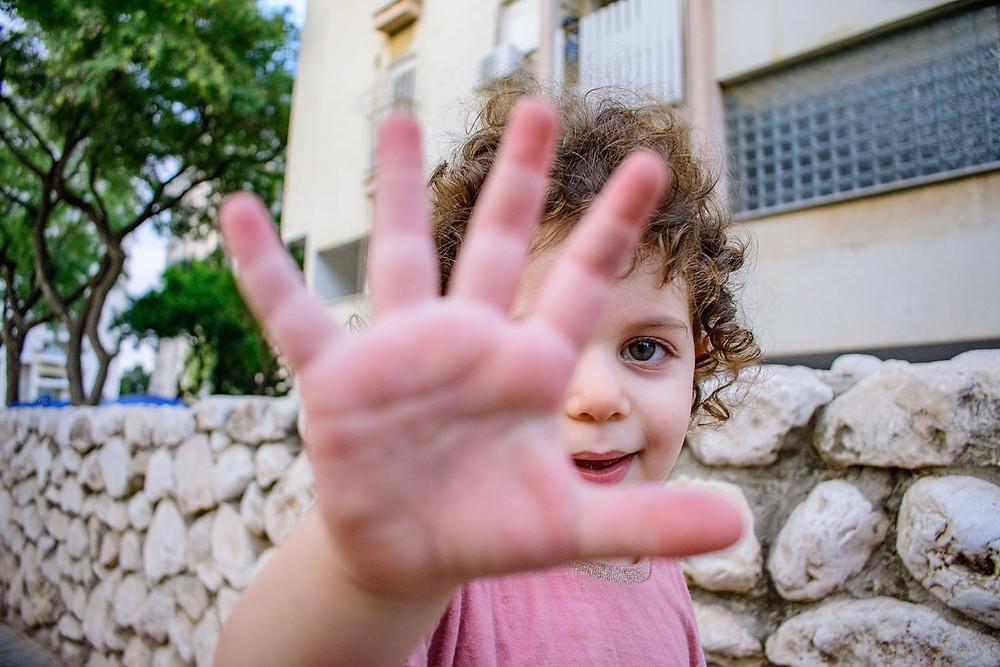 צילום ילדים ומשפחות - ילדה מנופפת לשלום