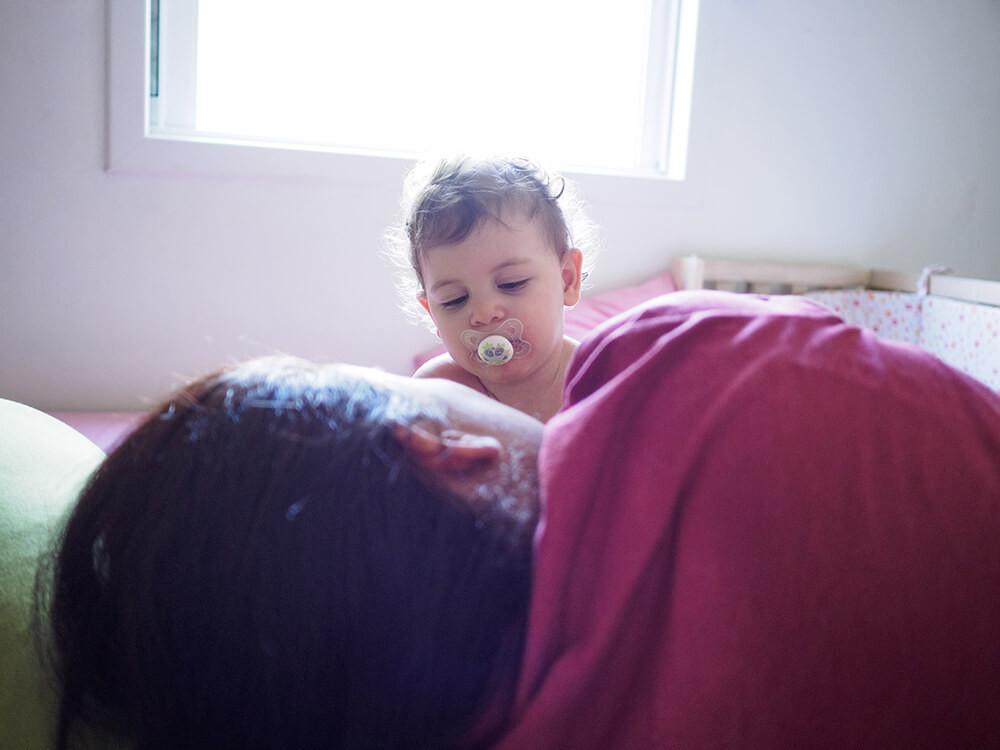 צילום ילדים ומשפחות - תינוקת עם מוצץ בפה יחד עם אמא במיטה