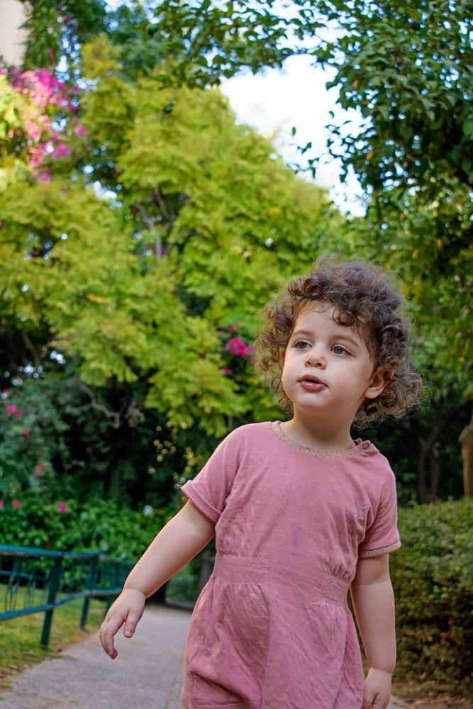צילום ילדים ומשפחות - ילדה מטיילת בגינה ציבורית