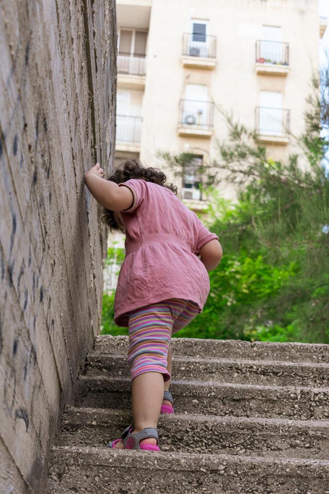 צילום ילדים ומשפחות - ילדה עולה במדרגות בטון