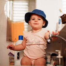 צילום ילדים ומשפחות  - תינוקת מחזיקה בברז