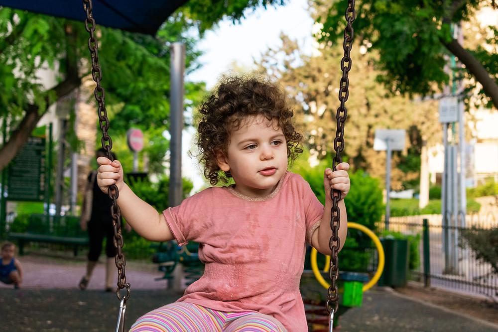 צילום ילדים ומשפחות - ילדה מתנדנדת בגינה ציבורית