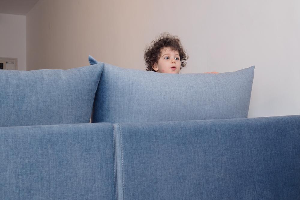 צילום ילדים ומשפחות - ילדה מטפסת על ספה כחולה