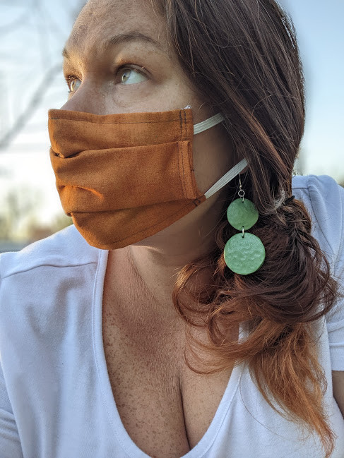 profile of woman in orange mask and green earrings