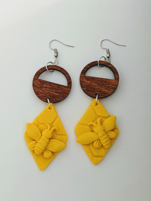 handmade earrings with wooden circle and a yellow diamond with yellow bee hanging from it