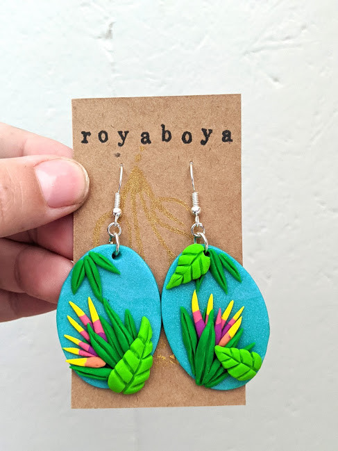 hand holding pair of oval turquoise earrings with tropical leaves and flowers