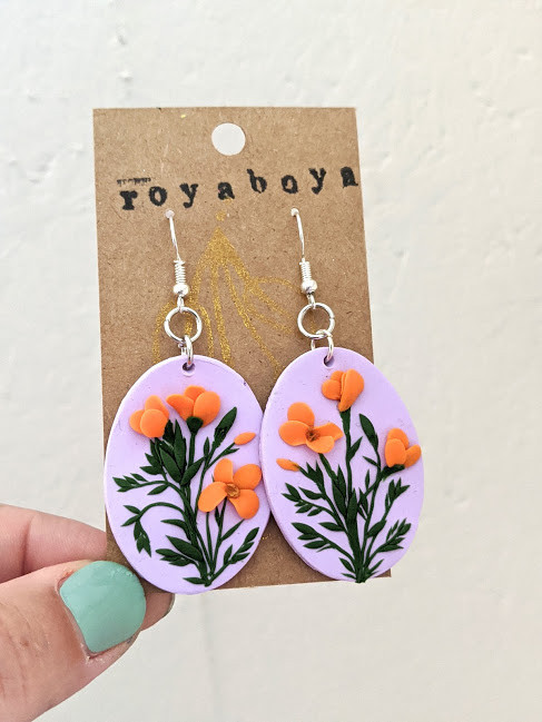 hand  holding pair of purple oval earrings with clay poppies