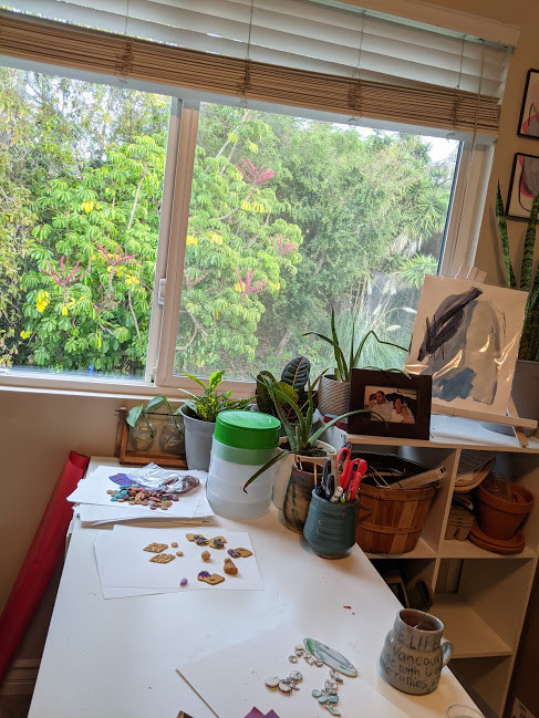cluttered desk in front of a window