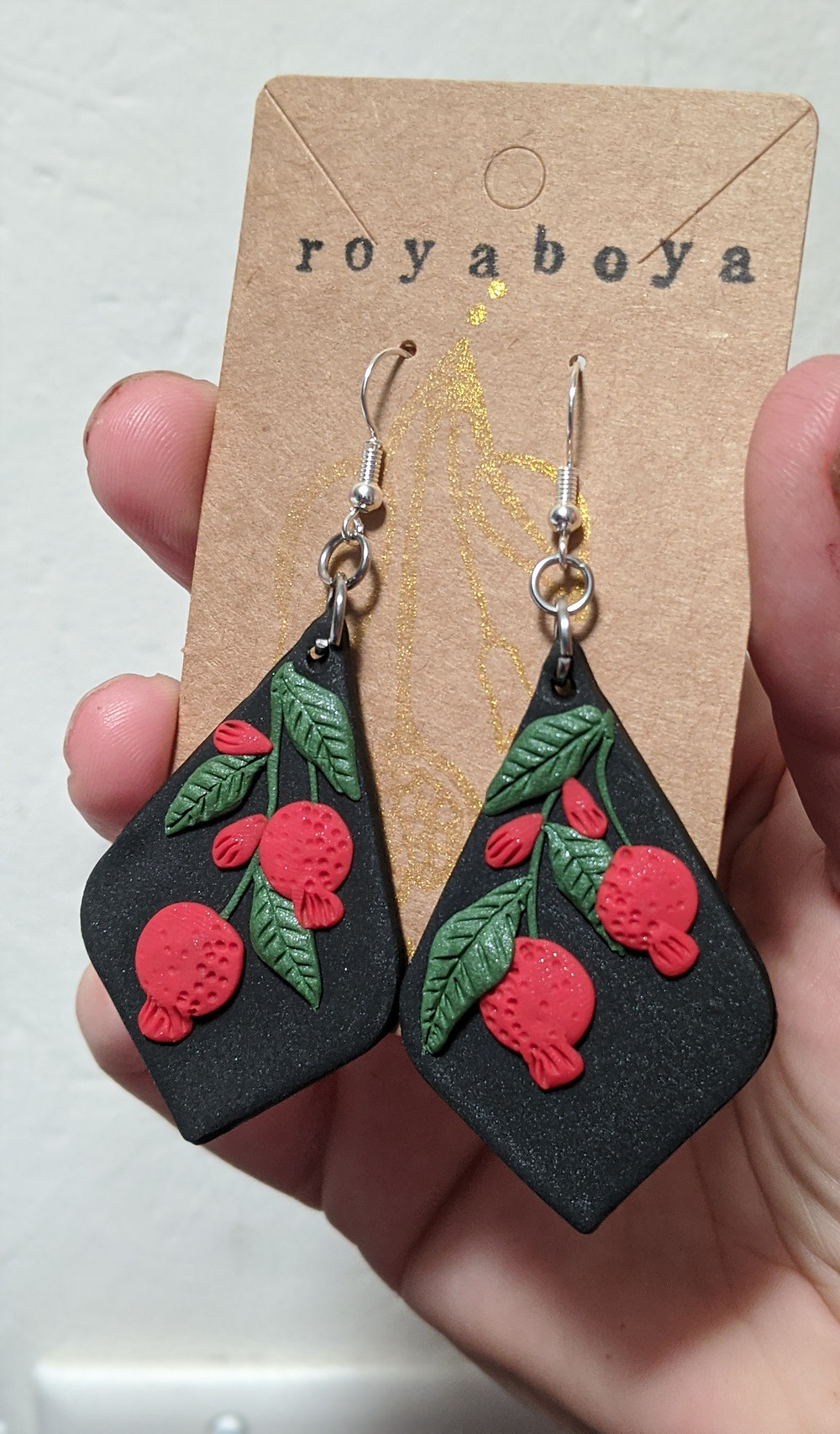 hand holding handmsde clay earrings that are black with red pomegranates